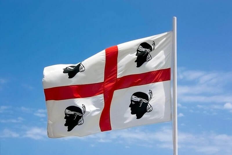 sardische Flagge i quattro mori im Wind wehend vor blauem Himmel